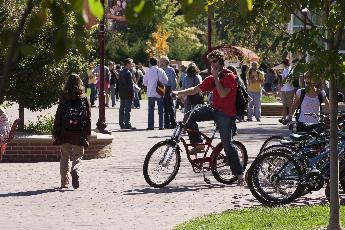 students biking on campus